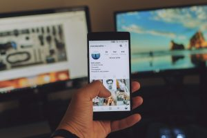 Hand holding a cell phone showing an Instagram page, two computer screens in the background. Photo by Erik Lucatero on Unsplash. Instagram for Writers on MultiTalented Writers.