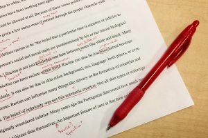 paper with typing and red corrections, with a red pen on top.