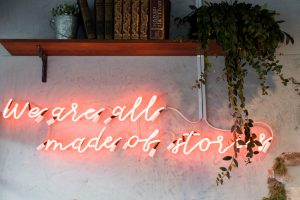 "Red neon sign on wall under a bookshelf reads ""We are all made of stories."" Literary magazines that pay on MultiTalented Writers. Photo by S O C I A L . C U T on Unsplash"