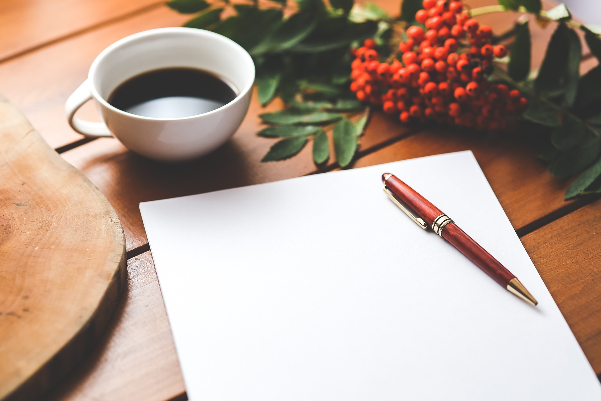 coffee, white paper, pen, and red berries on wooden table. Photo by Karolina Gabrowska on Pixabay