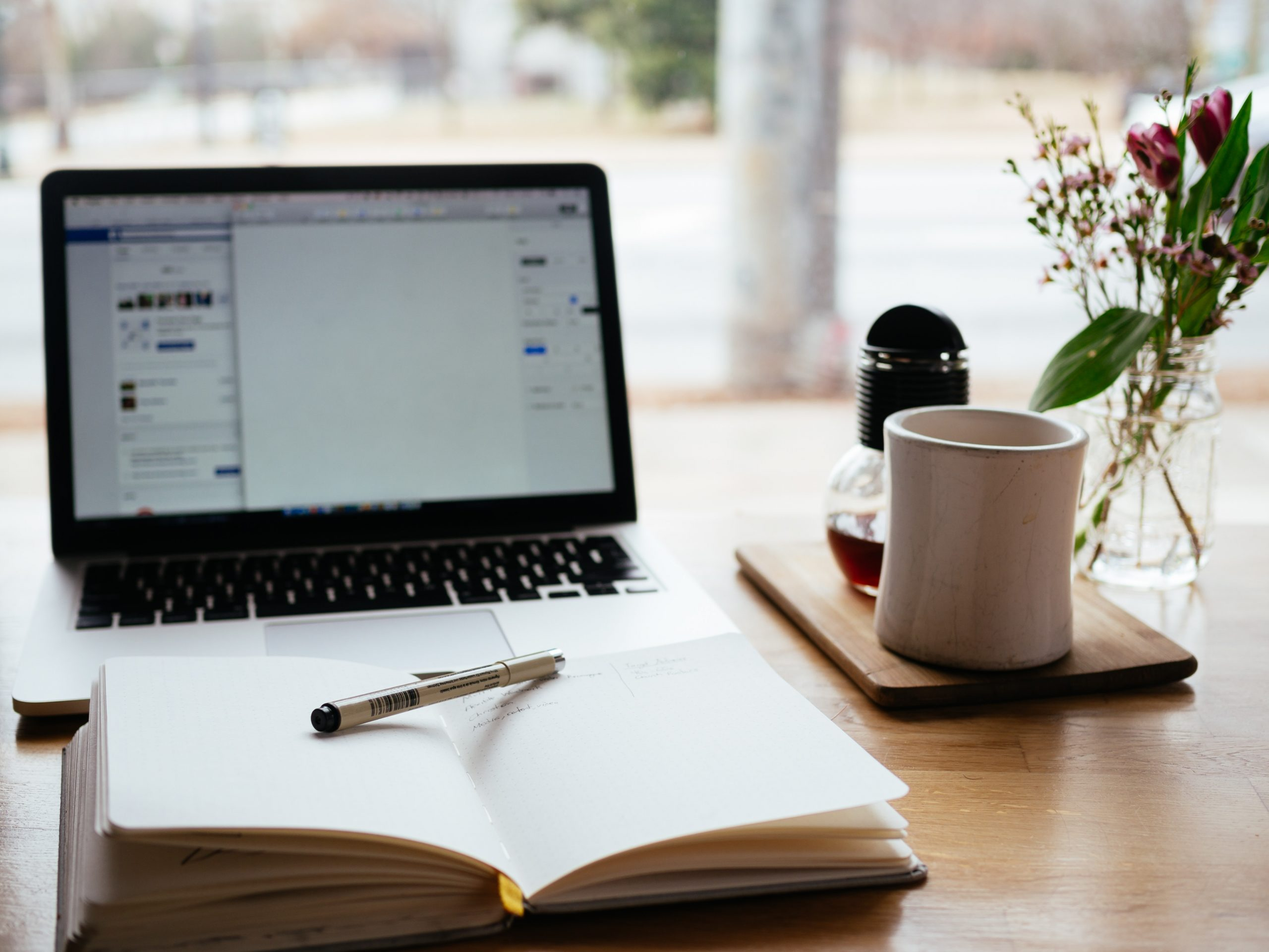 Get paid for your writing. Picture of a desk with a laptop, notebook and pen, mug, and plant. Photo by Nick Morrison on Unsplash.