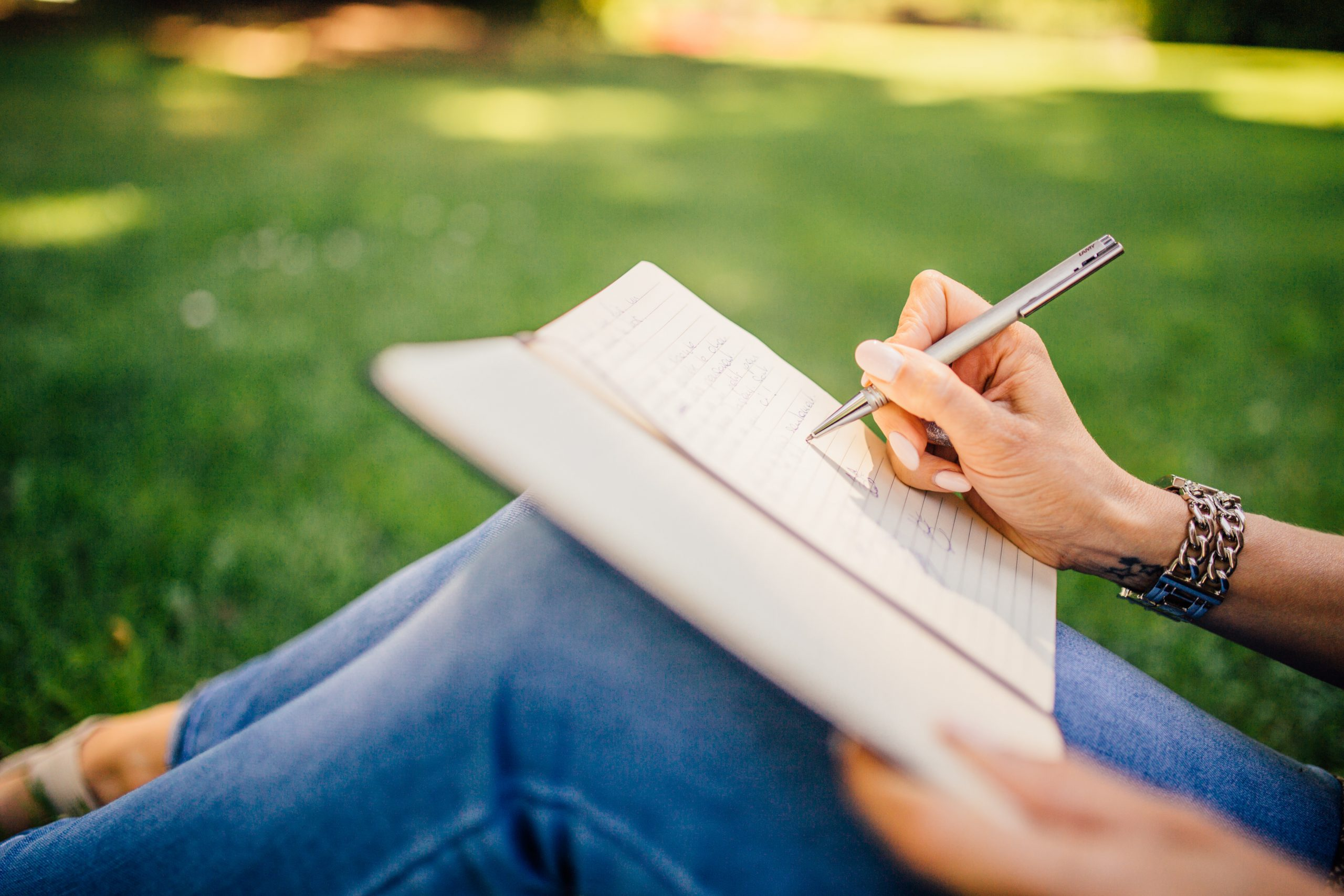 Person writing on a notebook that is resting on their knees. Only the legs and hands are visible.