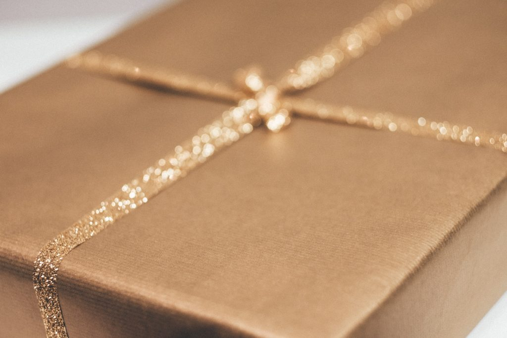 gift wrapped iin brown paper with a gold bow. photo from freestocks on Unsplash